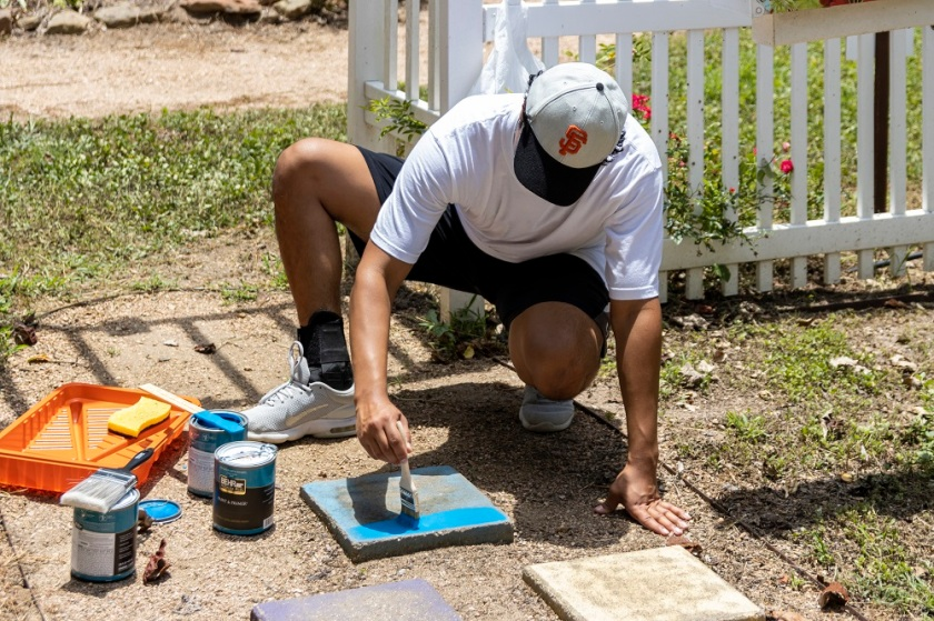 Intern Sebastian Morales paints at the Wynne Home.